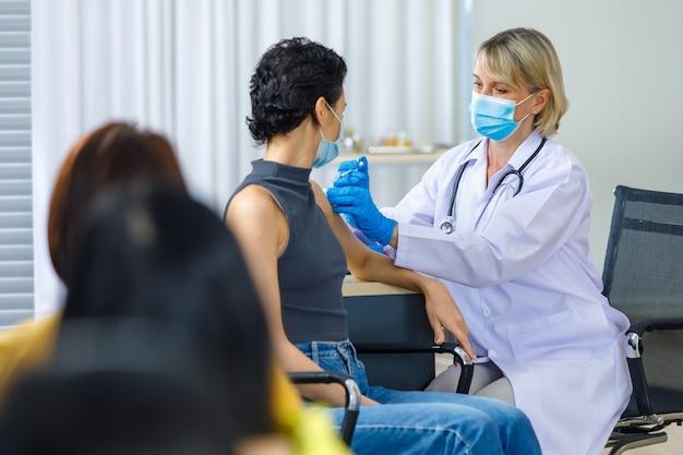 他の患者が列に並んで待っているとき、白い白衣を着た白人女性医師が青い手袋と聴診器を肩に注射している間、かわいい女性はフェイスマスクを着用してカメラを見て座っています。