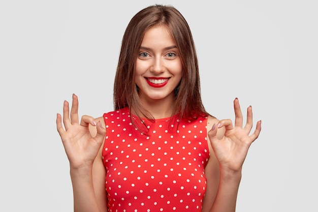 Cute female with charming friendly smile, makes okay gesture, dressed in fashionable polka dot dress, shows approval, poses against white wall. young woman with red lips models indoor.