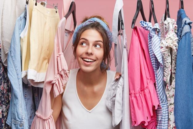 ハンガーに洋服を着て、おしゃれなドレスやブラウスを夢見て夢のような表情のかわいい女性。週末に友達と買い物に行くことについて空想にふける愛らしい女性