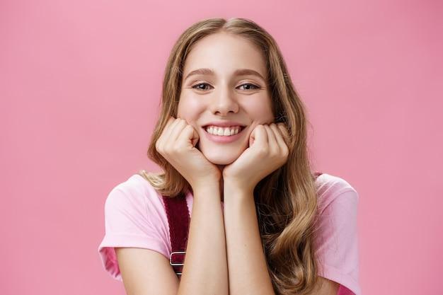 ピンクの背景の上に夢のような広い笑顔と賞賛の視線で面白い物語を見つめるように手に頭をもたれているタトゥーとウェーブのかかった髪を持つかわいいフェミニンで優しい素敵な女の子。
