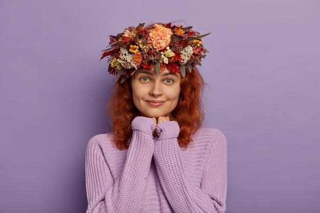 波状の赤い髪のかわいいフェミニンな女の子は、懇願するように手を握りしめ、大きな瞬間を予期し、特大のニットセーター、秋の花輪を身に着けています