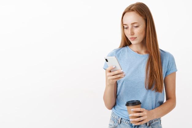 デバイスの画面を見てコーヒーカップと電話のメッセージングを保持しているスマートフォンでメモを書くことに集中している青いtシャツでかわいい女性の赤毛の女性