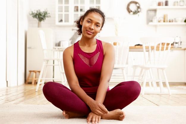 Giovane donna dalla pelle scura in forma carina in abiti sportivi alla moda seduto a piedi nudi sulla stuoia con le gambe piegate. ragazza nera attiva in buona salute che si rilassa in padmasana dopo la pratica di yoga