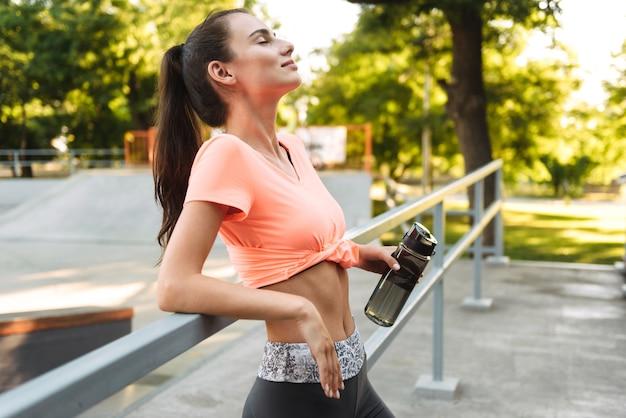 운동복에 귀여운 피트니스 소녀 미소하고 운동장에 난간에 굽힘 동안 물병을 들고