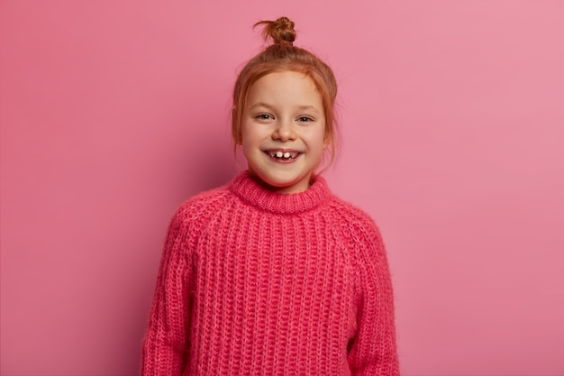 Cute five year old girl poses , expresses positive emotions, has ginger hair, wears warm winter sweater, glad to be photographed, poses against pink wall. sincere emotions and kids.