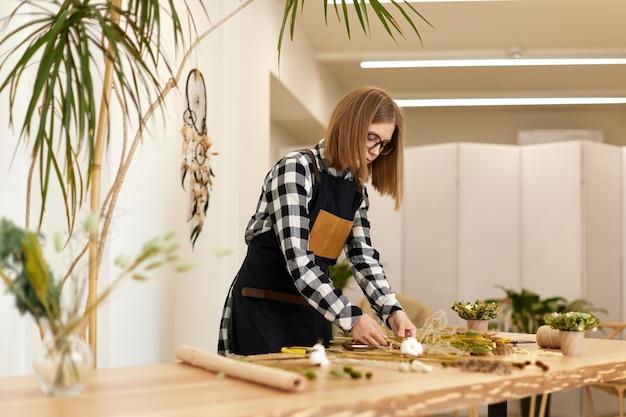 Симпатичный флорист делает красивый букет из сухоцветов на деревянном столе