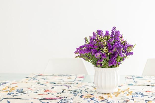 Милая цветочная композиция с фиолетовой статицей, украшающая обеденный стол