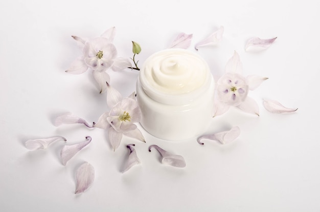 Cute flowers and petals and a jar of natural body cream isolated