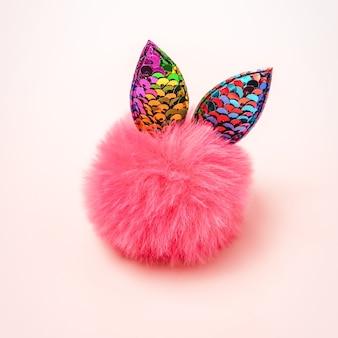 파스텔 배경에 귀와 귀여운 솜 털 공 장난감. 배려, 거룩함, 놀라움의 개념