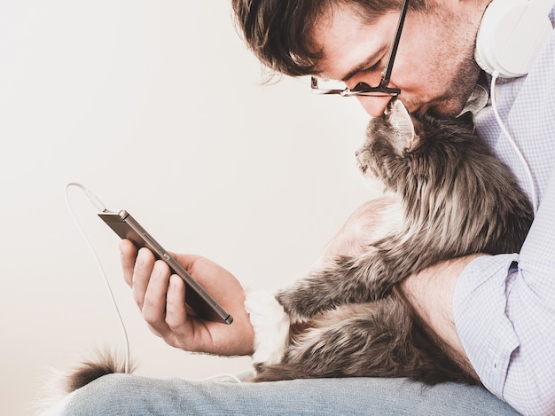 かわいい、ふわふわの子猫と電話を持つ男。ペットケアのコンセプト