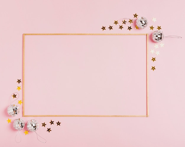 Cute frame with christmas balls on pink background