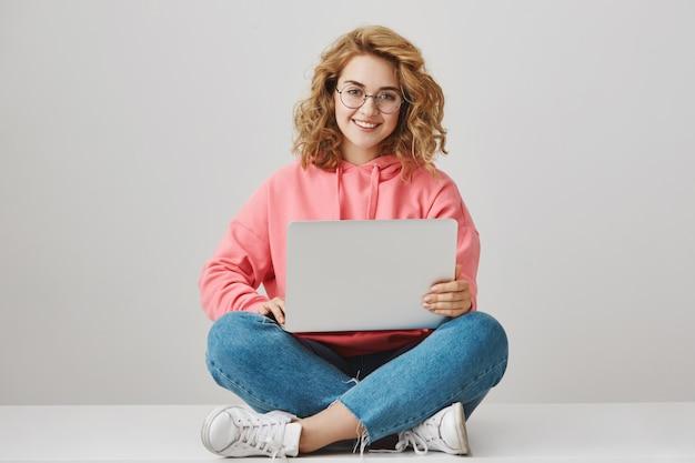 Симпатичная девушка-фрилансер с помощью ноутбука, сидя на полу и улыбаясь