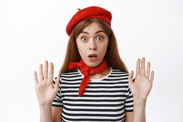 見えないガラスに寄りかかっているかのように手を上げて、白い壁に立ってパントマイム俳優を演じるかわいいフランスの女の子