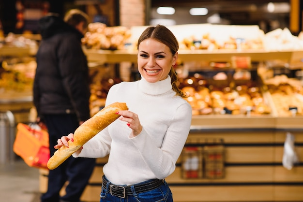 Cute frenchwoman in a striped t-shirt holding a baguette in the hands