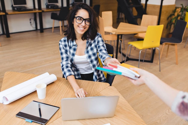 Carina giovane donna bruna amichevole in occhiali neri al tavolo prendendo libri e sorridendo al cliente. studiare all'università, lavorare come libero professionista, grande successo, grande squadra.