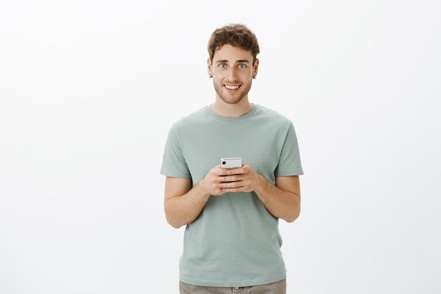 Симпатичный дружелюбный европейский светловолосый парень с щетиной в повседневной одежде, держит смартфон, широко улыбается и надеется найти любовь в новом приложении для своего новенького устройства