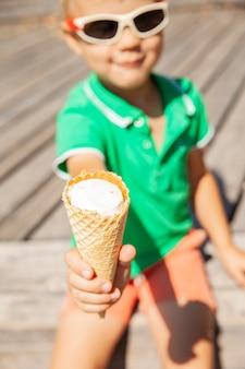 夏の公園で休んでいる間、笑顔でカメラでおいしいアイスクリームコーンを提供するスタイリッシュなサングラスのかわいいフレンドリーな男の子