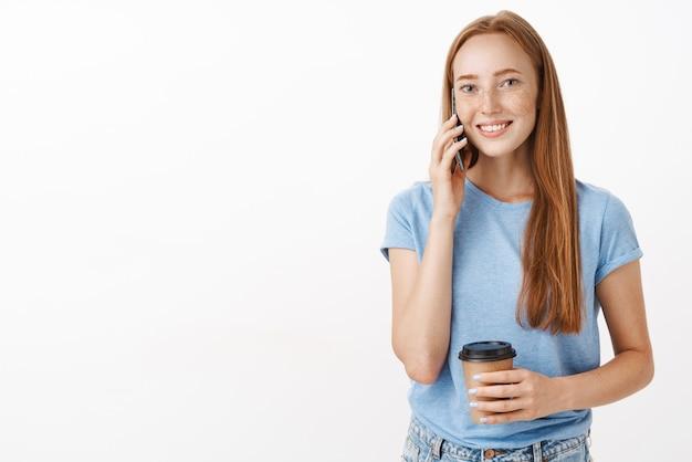 Carina ragazza rossa amichevole invitando il compagno a bere un caffè nella caffetteria con il suo smartphone in mano vicino all'orecchio e bicchiere di carta che sorride ampiamente pur avendo una piacevole conversazione sul muro grigio
