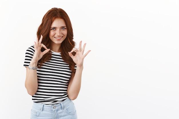 Симпатичная дружелюбная рыжая девочка-подросток в полосатой футболке, одобряет, полностью соответствует вашему выбору, удовлетворенно улыбается, показывает жест разрешения, оценивает отличную идею, белая стена
