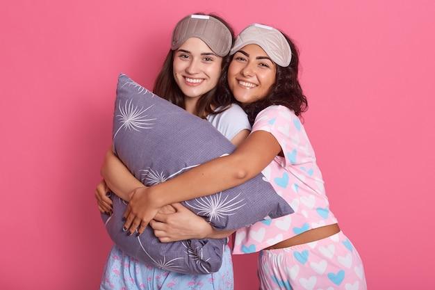 Милая девушка друзей в ночном костюме для пижамной вечеринки на розовом фоне