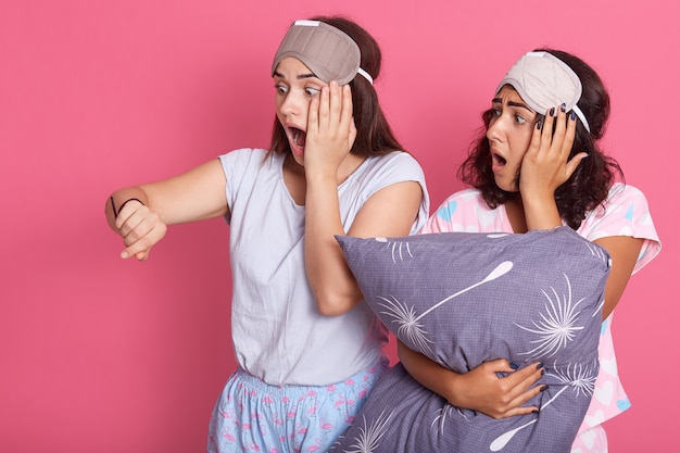 ピンクの背景のパジャマパーティーの夜のスーツでかわいい友達の女の子