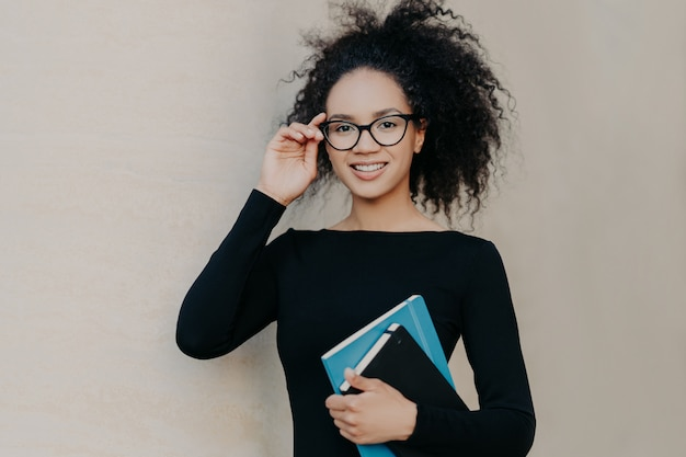 Cute frizzy young woman with gentle smile, keeps hand on rim of glasses, wears casual black jumper, holds notepad