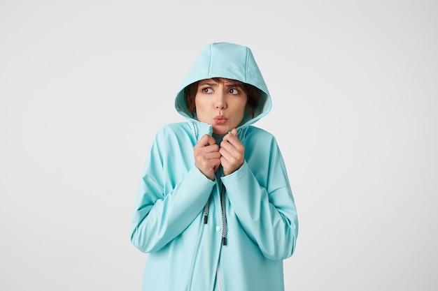 白いゴルフと水色のレインコートを着たかわいい凍った短い髪の巻き毛の女性は、雨からボンネットの下に隠れて目をそらし、白い背景の上に立っています。