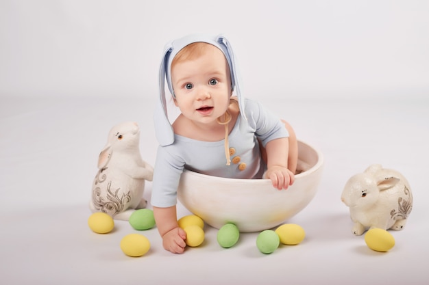 Cute funny baby boy with bunny ears and colorful easter eggs and rabbits. easter baby. greeting easter card template.