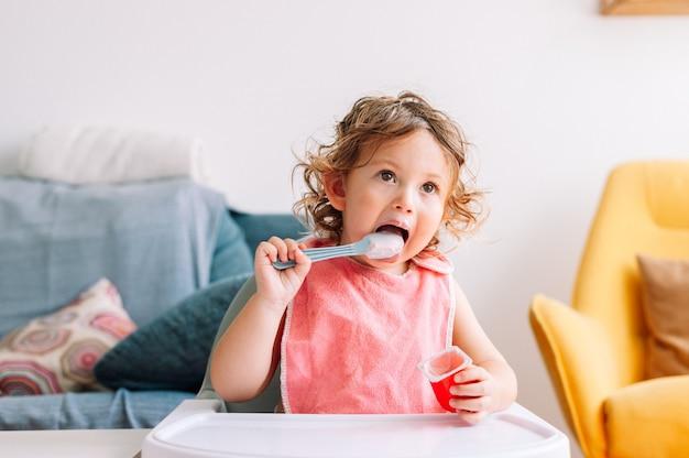 그의 입에 숟가락으로 앉아 귀여운 재미 아기 소녀 2 세