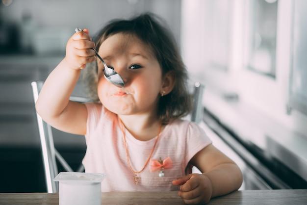 午後にピンクのドレスを着てキッチンでヨーグルトを食べるかわいい、面白い女の赤ちゃんかわいい