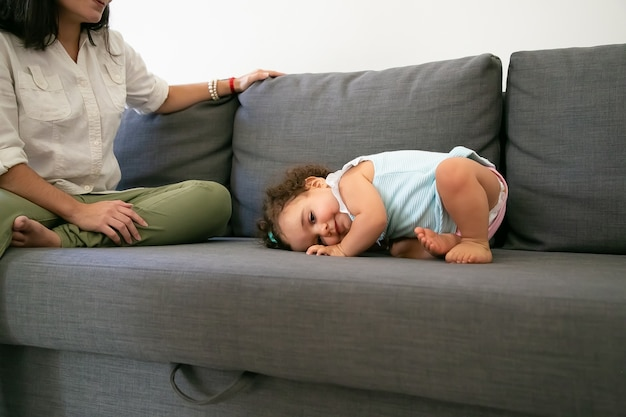 ママの近くの灰色のソファに横たわっている淡いブルーのドレスのかわいい面白い女の赤ちゃん。クロップドショット。親子関係の概念