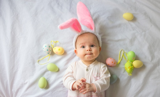 Cute funny baby with bunny ears and colorful easter eggs at home on a white background