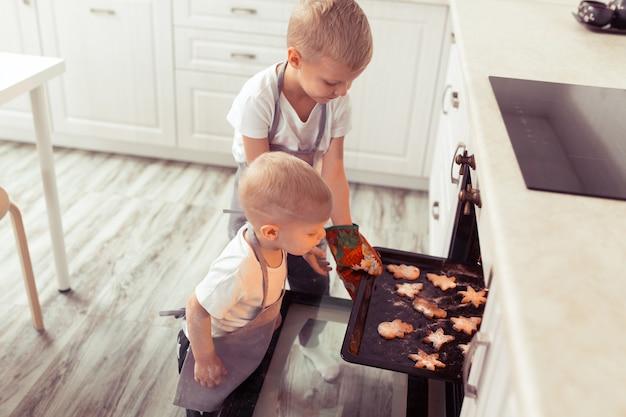ジンジャーブレッドクッキーを調理して準備するかわいい面白い金髪の子供男の子