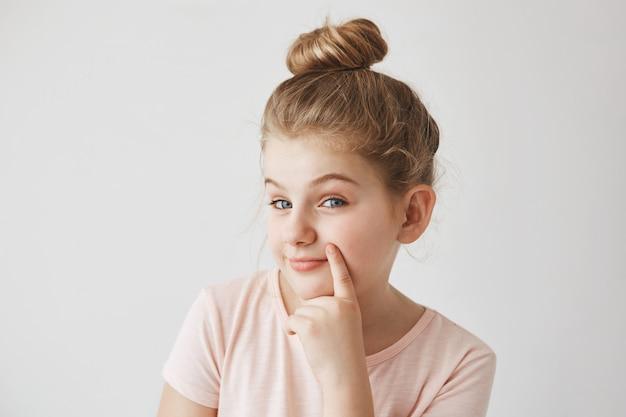 上げられた眉毛と卑劣な表情で、唇の近くにパン髪型保持指でかわいい面白い金髪少女。