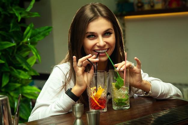 귀여운 재미있는 갈색 머리 소녀는 동시에 두 개의 칵테일을 마시고 앞에 웃고