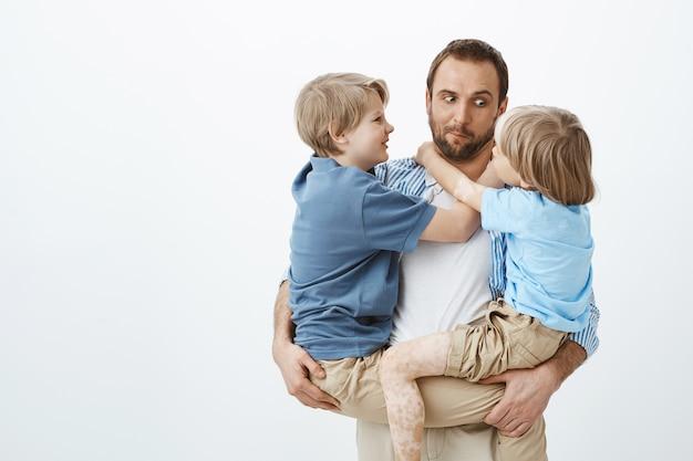 Милый забавный кавказский отец держит двух сыновей на руках, смотрит на младшего мальчика и корчит рожи, позитивный и счастливый, имея отличных детей