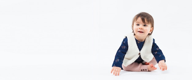 Cute funny fashionable small smiling girl sitting in studio posing on white background