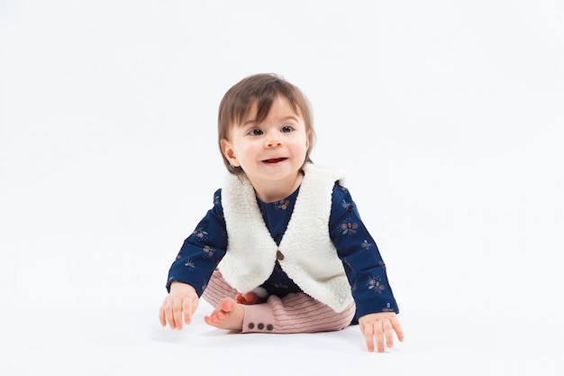 Cute funny fashionable small smiling girl sitting in studio posing