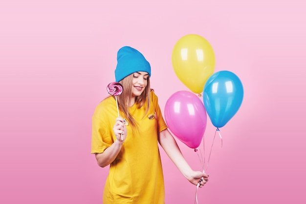 Cute funny girl in blue cap portrait holds an air colorful balloons and lollipop smiling on pink . beautiful multicultural caucasian girl smiling happy