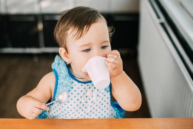 とても甘い青いドレスを着てキッチンで日中にヨーグルトを食べるかわいい、面白い女の子