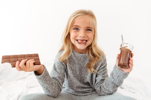 초콜릿을 들고 그녀의 더러운 이빨을 보여주는 귀여운 재미 있은 소녀