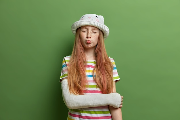 Cute funny girl makes grimace and pouts lips , has freckled face and long foxy hair, poses with cast on broken arm, got injury during summer vacation, wears striped t shirt and hat.