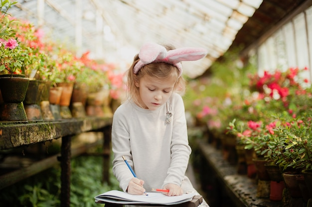 Cute funny girl with easter bunny ears at garden. easter concept. laughing child at easter egg hunt
