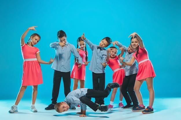 Милые смешные девочки и мальчики танцуют на синем