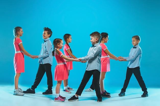 Милые веселые девочки и мальчики танцуют