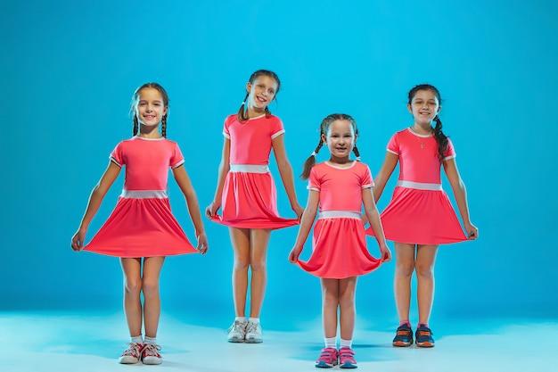 Cute funny girls dancing on blue