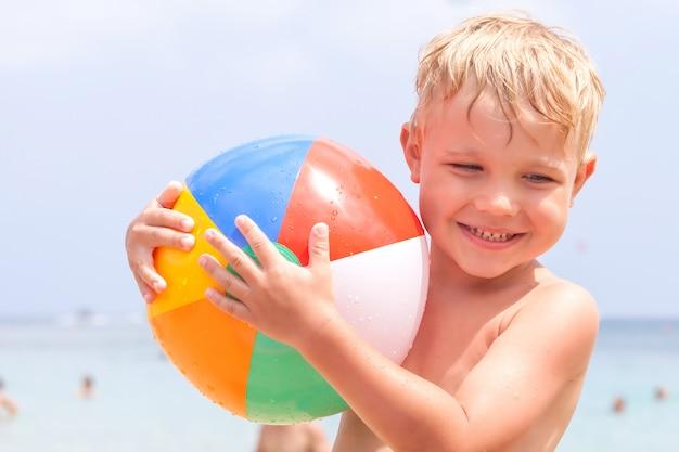 Милый забавный счастливый маленький мальчик, играющий в волнах воды в морском океане в солнечный день