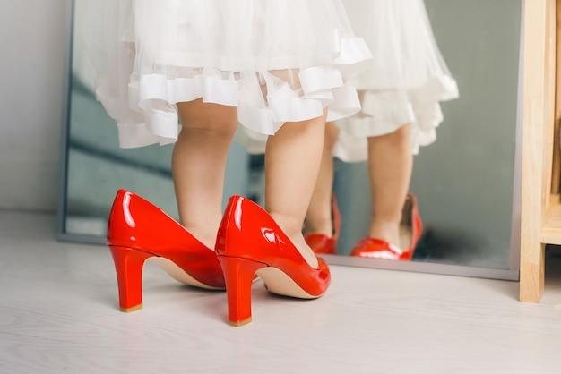 귀엽고 재미있는 어린 소녀가 집에서 엄마의 빨간 하이힐을 신고 걸어갑니다