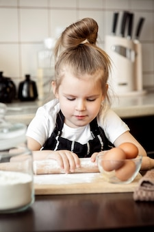 Cute funny little girl in house kitchen alone prepared surprise for mom on mothers day.
