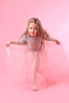 ピンクの背景にジャンプする長いブロンドの髪を持つかわいい面白い女の子